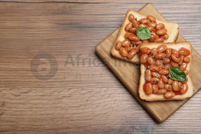 Toasts with delicious canned beans on wooden table, top view. Space for text
