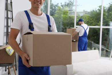Moving service employees with cardboard boxes in room, closeup