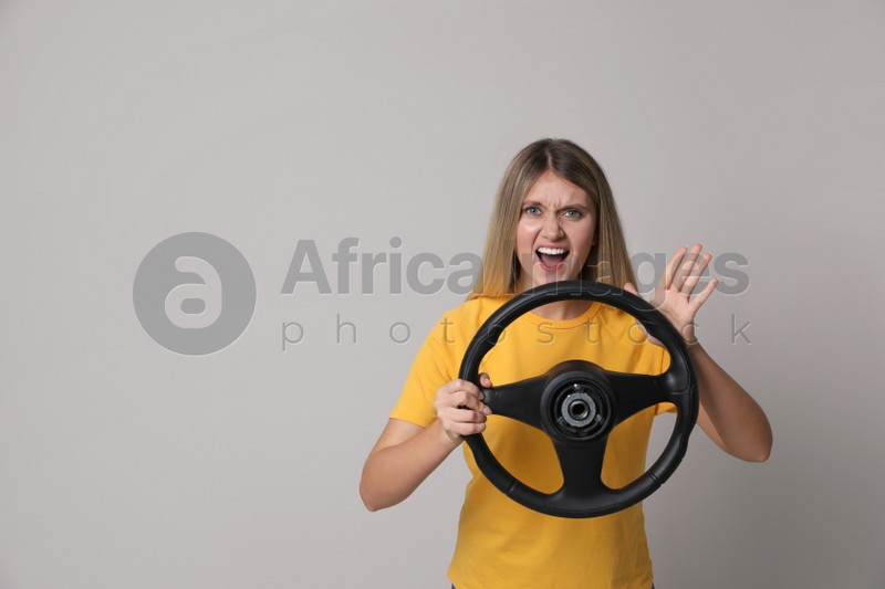 Emotional young woman with steering wheel on grey background. Space for text