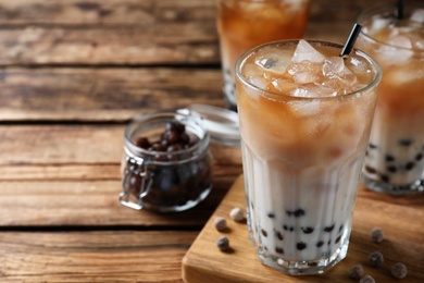 Tasty milk bubble tea on wooden table, closeup. Space for text