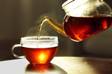 Pouring fresh hot tea from teapot into cup against blurred background, closeup