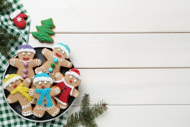 Delicious Christmas cookies and fir branches on white wooden table, flat lay. Space for text