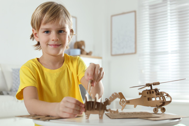 Little boy making carton toys at table indoors. Creative hobby