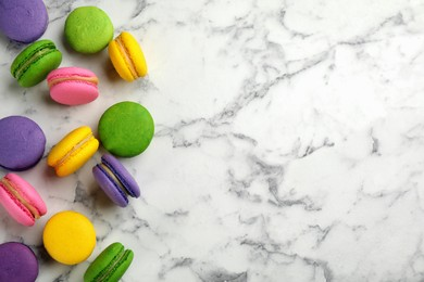 Delicious colorful macarons on white marble table, flat lay. Space for text