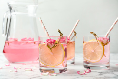Refreshing drink with lemon and rose on white marble table