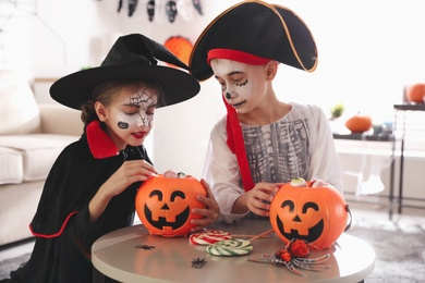 Cute little kids with pumpkin candy buckets wearing Halloween costumes at home