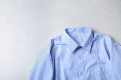 Stylish light blue shirt on light table, top view with space for text. Dry-cleaning service