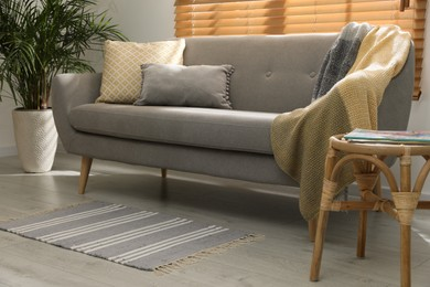 Stylish striped rug with fringe and comfortable sofa in living room. Interior design