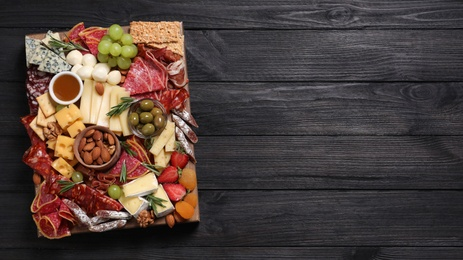 Assorted appetizers served on black wooden table, top view. Space for text