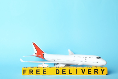 Toy plane and cubes with words FREE DELIVERY on light blue background, space for text. Logistics and wholesale concept