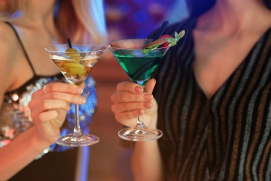 Young women with martini cocktails in bar, closeup