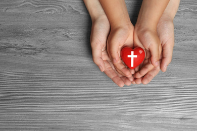 Woman and child holding heart with cross symbol on grey wooden background, top view with space for text. Christian religion