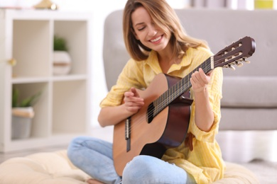 Young woman playing acoustic guitar at home