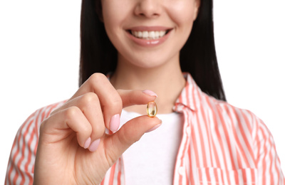 Young woman with vitamin capsule on white background, closeup