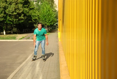 Handsome young man roller skating near yellow building, space for text