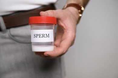 Donor holding container with sperm on beige background, closeup. Space for text