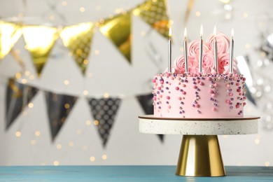 Beautifully decorated birthday cake on turquoise wooden table against blurred festive lights, space for text