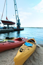 Modern kayaks with paddles on beach near river. Summer camp activity