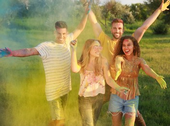 Happy friends having fun with colorful powder dyes outdoors. Holi festival celebration