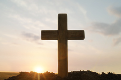 Wooden Christian cross outdoors at sunrise. Religion concept