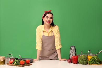 Young housewife at white table with vegetables and different utensils on green background