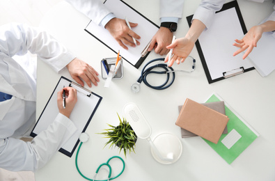 Doctors having meeting at table in office, top view