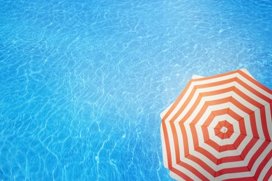 Open beach umbrella and swimming pool. Summer vacation