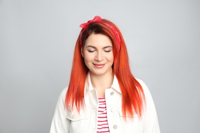 Young woman with bright dyed hair on grey background