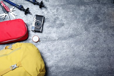 Flat lay composition with tourist backpack and other different camping equipment on grey background, space for text