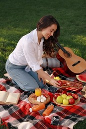 Happy young woman having picnic on plaid outdoors