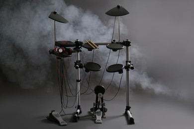 Modern electronic drum kit and smoke on grey background. Musical instrument
