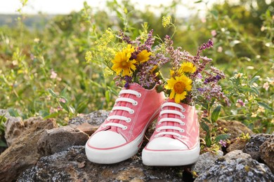 Shoes with beautiful flowers on stones outdoors