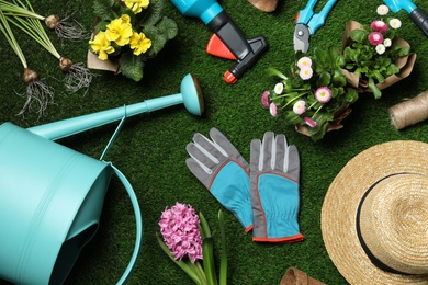 Flat lay composition with gardening equipment and flowers on green grass