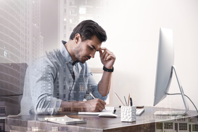 Double exposure of architect working at table and buildings