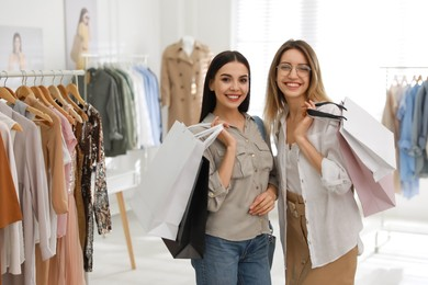 Young women with shopping bags choosing clothes in modern boutique