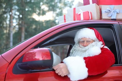 Authentic Santa Claus in red car, view from outside