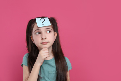 Pensive girl with question mark sticker on forehead against pink background. Space for text