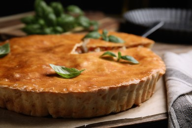 Delicious pie with meat and basil on wooden board, closeup