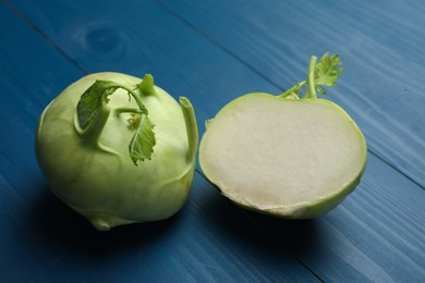 Whole and cut kohlrabi plants on blue wooden table