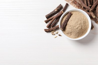 Powder in bowl and dried sticks of liquorice root on white table, flat lay. Space for text
