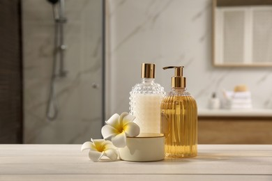Composition with liquid soap in glass dispenser on white wooden table indoors