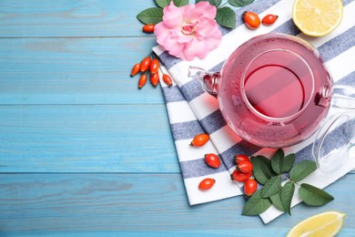 Fresh rose hip tea and berries on blue wooden table, flat lay. Space for text