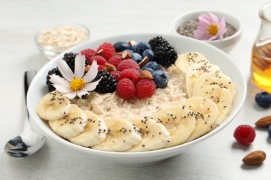 Tasty oatmeal porridge with berries, banana and chia seeds served on light wooden table, closeup