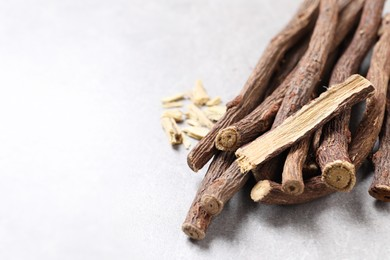 Dried sticks of liquorice root on grey table, closeup. Space for text