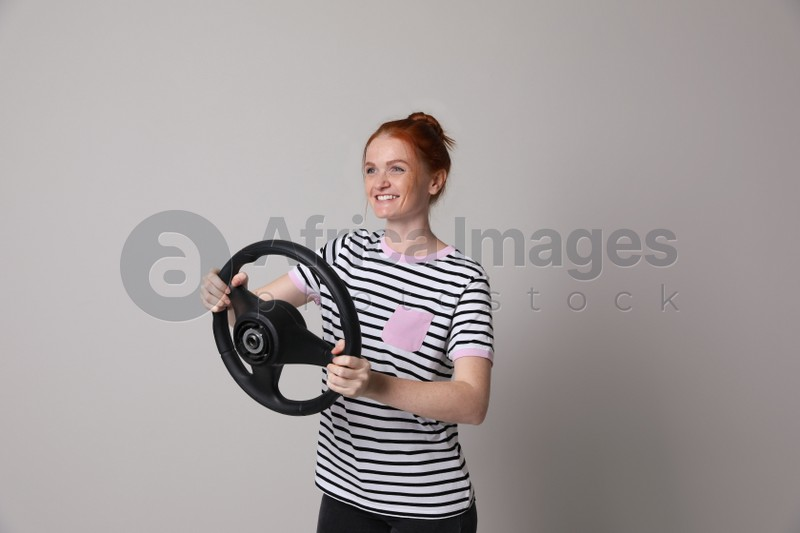 Happy young woman with steering wheel on grey background