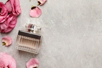 Flat lay composition with bottle of perfume and eustoma flowers on grey textured background, space for text
