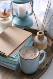 Wooden tray with books, air reed freshener and cup of coffee on white table indoors