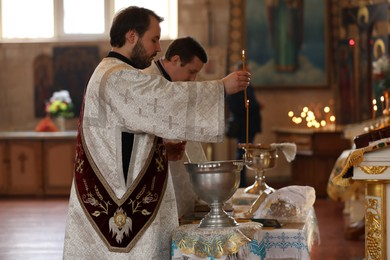 MYKOLAIV, UKRAINE - FEBRUARY 27, 2021: Deacon and priest conducting baptism ceremony in Kasperovskaya icon of Mother of God cathedral