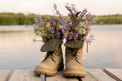 Boots with beautiful wild flowers on wooden pier near lake