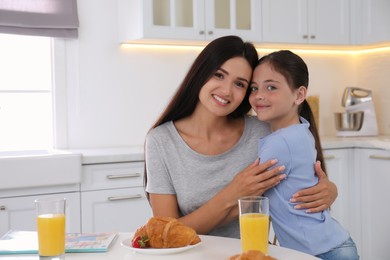 Portrait of happy mother and daughter in kitchen. Single parenting